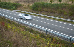 Vehicle in motion. Silver vehicle in motion on motorway, car transportation Royalty Free Stock Image