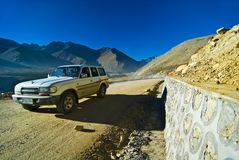 Vehicle on mountain road. Vehicle travelling on remote road with mountainous Tibetan landscape in background Royalty Free Stock Image