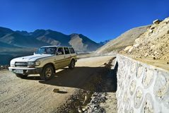 Vehicle on mountainous road. Single vehicle traveling on remote road through Himalaya mountains, Tibet Royalty Free Stock Photography