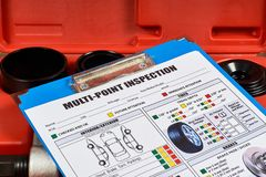 Vehicle multi-point inspection report form. Vehicle multi-point inspection form against the background of automotive tools. Close up stock photography