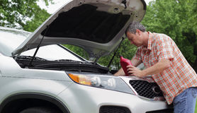 Vehicle Owner Checks Oil. A mature man vehicle owner checking and adding oil to his vehicle at home before a long trip Royalty Free Stock Image