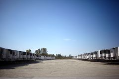 Vehicle park full of haulage trailers for freight. Parked in two long receding rows under a cloudless blue sky Stock Image