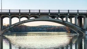 Vehicle and pedestrian crossing bridge spanning across a river during golden hour royalty free stock photography