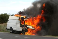 Vehicle with Raging Fire. Delivery type vehicle on side of road burning with large flames and smoke Stock Photography