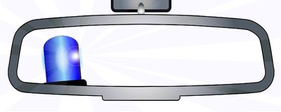 Police in the Rear View Mirror. A vehicle rear view mirror showing a police vehicle flashing blue light Royalty Free Stock Photos