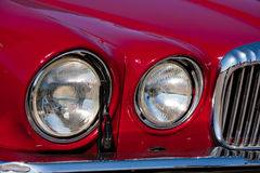 Vehicle's headlight. A photo of a red vehicle's round headlights and bold silver grille Royalty Free Stock Photos