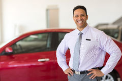 Vehicle sales consultant. Middle aged vehicle sales consultant inside showroom Royalty Free Stock Photo