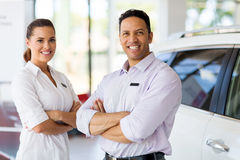 Vehicle sales staff. Cute vehicle sales staff with arms crossed in car showroom Royalty Free Stock Images