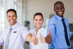 Vehicle sales team. Cheerful vehicle sales team giving thumbs up Royalty Free Stock Photo
