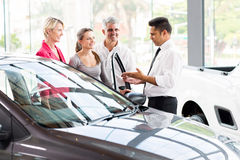 Vehicle salesman car family. Vehicle salesman showing new car to a family stock photo