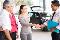 Vehicle salesman handshake customer. Vehicle salesman handshaking with young adult customer after the sale Royalty Free Stock Photo
