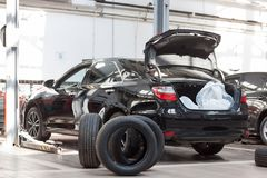 Vehicle is standing near a hydraulic lift. Scheduled replacement and wheel alignment in workshop car. Modern service stock photography