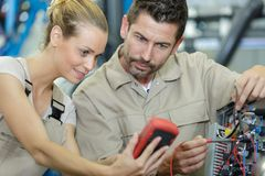 Vehicle technician showing voltmeter result. Result stock photo
