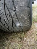 Bolt in damaged tire on vehicle royalty free stock photography