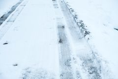 Vehicle tire tracks on road covered in snow and ice. Winter driving conditions.  stock photography