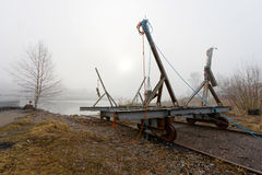 Vehicle to launch boats to the sea. Vehicle on rail road used to launch boats to the sea in the harbor a foggy morning stock image