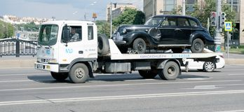 Vehicle towing. Tow truck transports an old car on the streets of Moscow Stock Images
