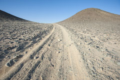 Vehicle tracks through an arid desert Royalty Free Stock Photography