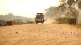 Vehicle on village road at sun set stock footage