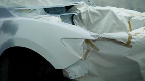 The vehicle that was in the accident is under repair in an auto service, the car is covered with a tarpaulin. The body of the modern machine is in the auto stock footage