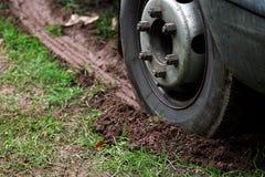 Vehicle wheel skidding on mud. Wheel of vehicle leaving skid marks on muddy, grass surface Royalty Free Stock Photography