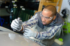 Vehicle worker fixing body. Vehicle worker fixing the body Stock Images