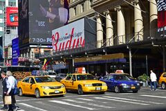 Vehicle yellow taxi cars stopping for traffic light pedestrian crossing in front of Hotel Pennsylvania Midtown Manhattan, New York