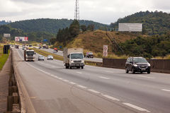 Vehicles on BR-374 highway with headlights on during the daylight obeying the new Brazilian transit laws Stock Photo