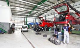 Vehicles in a car repair shop on the lifting platform for repair stock image