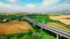Aerial view of driving vehicles by the highway between yellow and green grass. Aerial view of fields and rural settlements by summer sunny day in Tuscany stock video