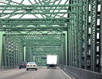 Vehicles Driving Across Bridge. This photo shows vehicles in two cars and one truck driving across a green metal bridge on a road Royalty Free Stock Images
