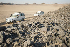 Vehicles driving through rocky desert stock photography