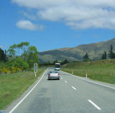 Vehicles on New Zeland highway. Scenic view of vehicles travelling on countryside highway with mountains in background, Christchurch, New Zealand Royalty Free Stock Photography