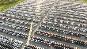 Vehicles parked on production plant parking lot at sunset. New coloured vehicles parked on production plant storage parking lot against forests at bright summer stock video footage