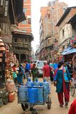 Vehicles and people occupying a busy shopping street in Kathmandu Stock Image