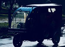 Vehicles running in the rain isolated unique photo. A three wheeler traditional Bangladeshi vehicles running on a wet road in the rain isolated unique photograph royalty free stock images