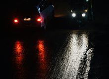 Vehicles running on the wet street at night. Vehicles running on the wet rainy streets at night isolated unique stock photograph stock image
