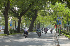 Vehicles traveling on a green street of Hanoi capital Stock Photography