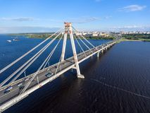 Vehicular cable-stayed bridge with vehicle flows on road lanes. Aerial view at the riverbank and part of carriageway. Cherepovets,. Vehicular cable-stayed bridge Royalty Free Stock Image
