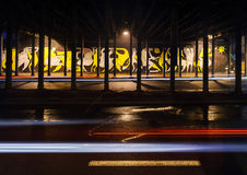 Vehicular light trails and graffiti on background in the night. Vehicular light trails and graffiti on the background under the bridge in Katowice, Poland Stock Image