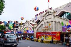 Veicoli che viaggiano su una via accanto al mercato di Dong Xuan della capitale di Hanoi Mercato di Dong Xuan di metà di festival fotografie stock