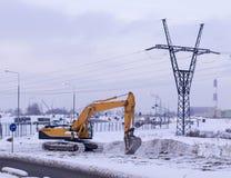 Veicolo dell'escavatore sul fondo della città all'inverno industriale, stagionale immagine stock