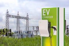 Veicolo elettrico che fa pagare la stazione di Ev e spina del rifornimento del cavo elettrico per l'automobile di Ev sulla sottos immagini stock