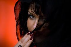 Through the veil. Portrait of young nice woman in black veil on red back Royalty Free Stock Photo