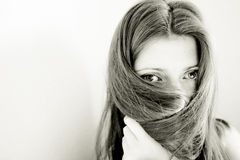 Veil of beauty. Young woman hiding her face with long straight brown hair Royalty Free Stock Image