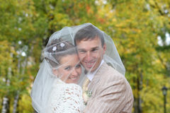 Veil covered bride and groom in autumn forest Royalty Free Stock Photos