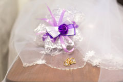 Veil, earrings, and a garter with a purple bow Stock Photo