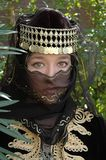 Veiled. A girl wearing a black veil and head dress with golden adornments Royalty Free Stock Photography