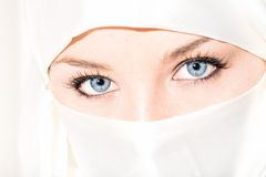 Veiled. Blue eyed girl wearing face veil royalty free stock photo