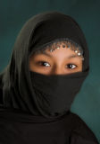 Veiled in black. Young arabian woman in a black veil Royalty Free Stock Image